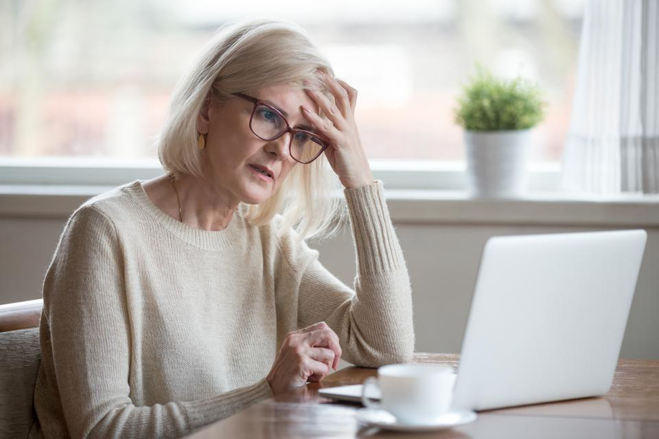 Confused mature woman thinking about online problem looking at laptop