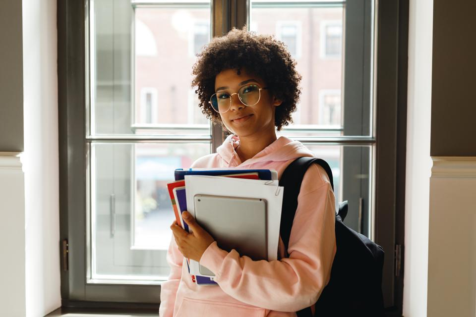 Teenage Girl Wearing Eyeglasses Holding Books At Home