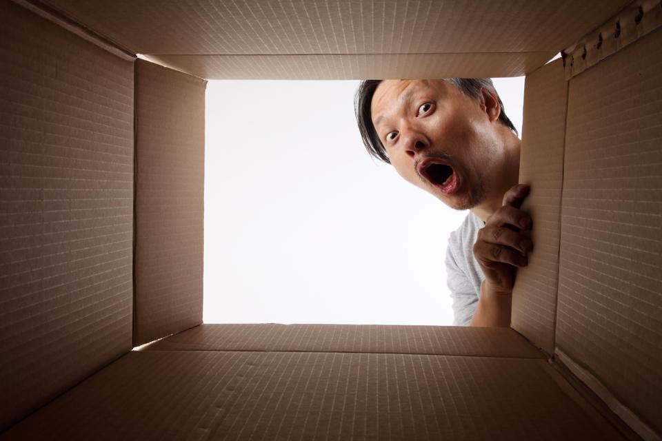 Portrait Of Shocked Man Peeking In Cardboard Box