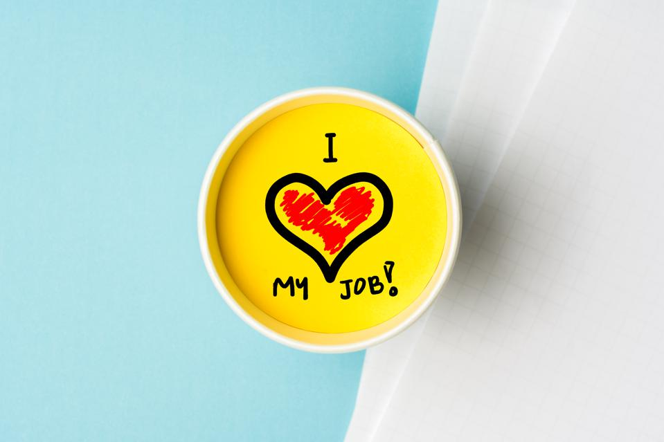 I love my job concept. Paper cup wint yellow top and blue background desk with notes.