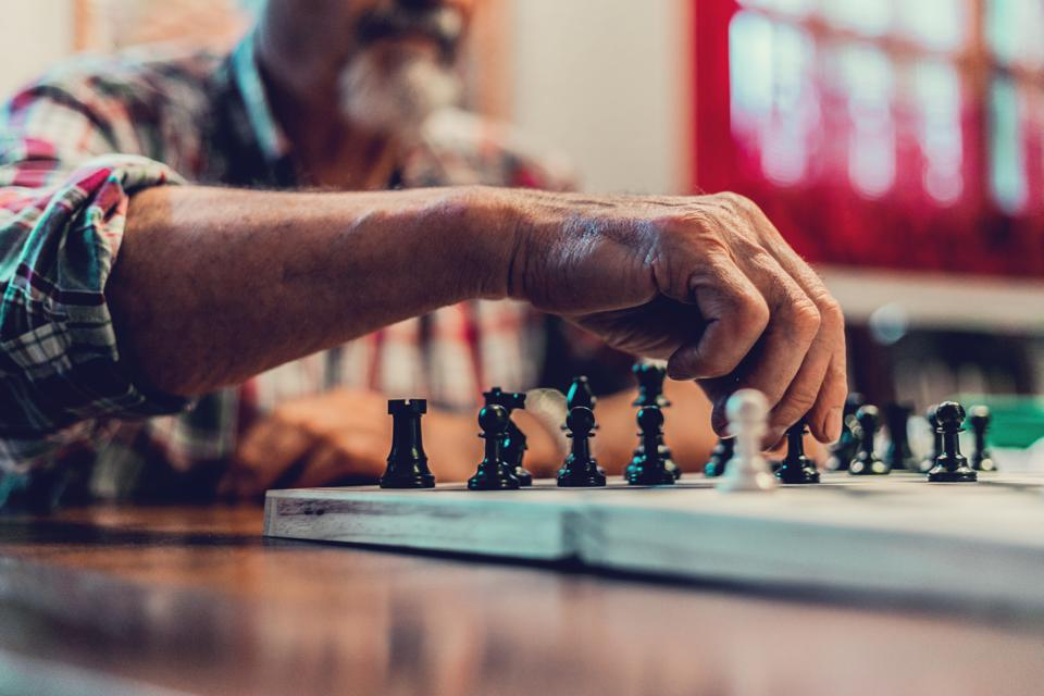 closeup hands senior man playing  chess