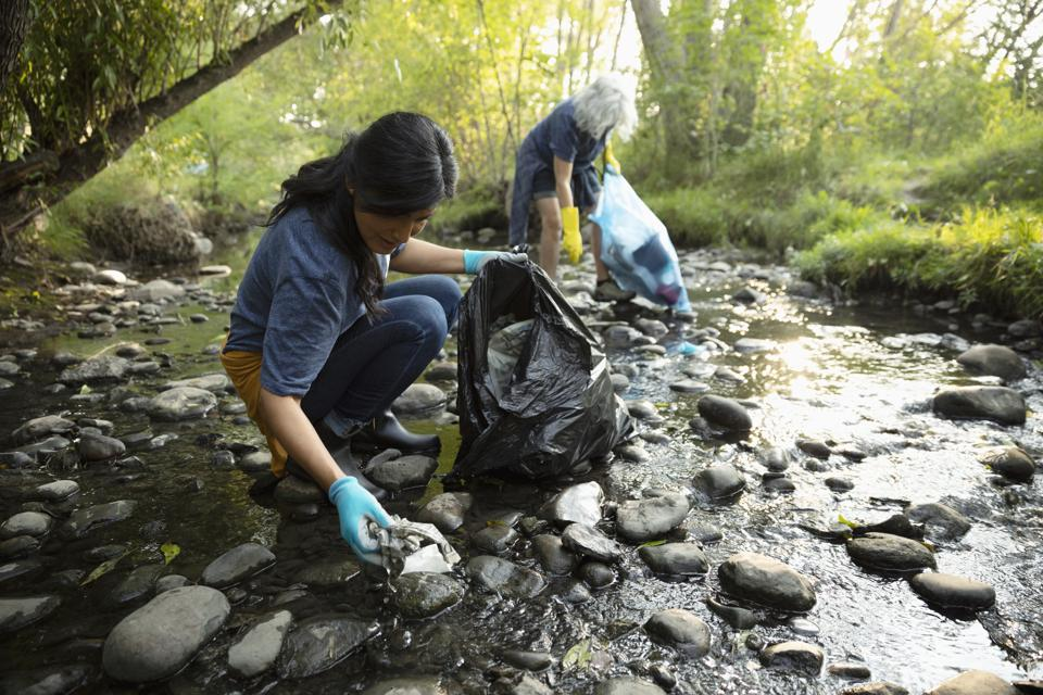Women cleaning up garbage in stream