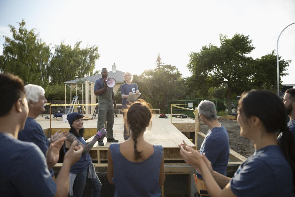 Volunteers meeting and clapping, helping build house