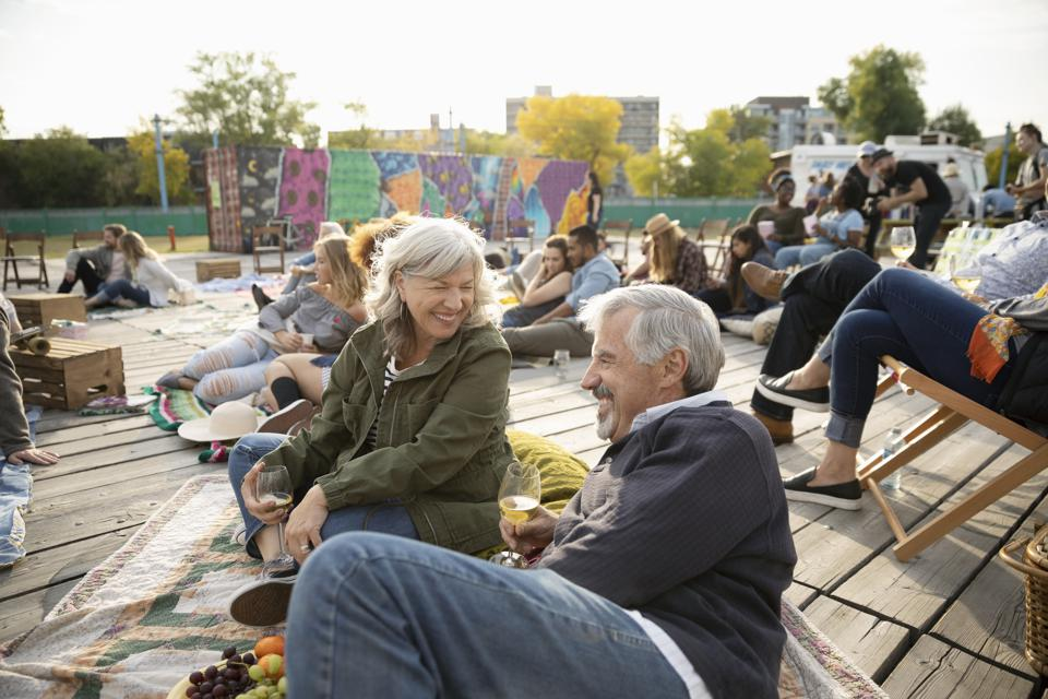 Happy senior couple relaxing, enjoying picnic and waiting for movie in park to start