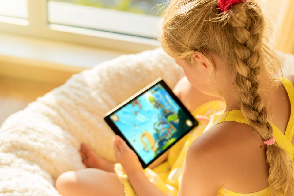 Girl playing game on tablet computer