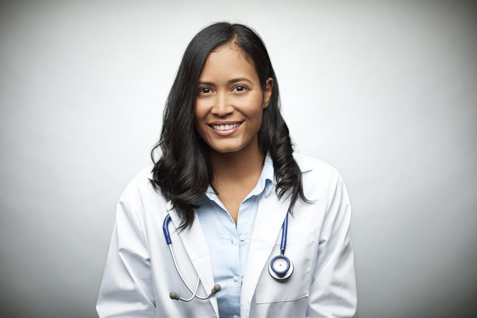 Female doctor smiling over white background