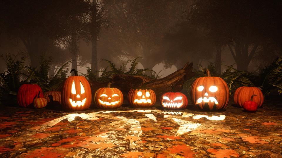 Jack-o-lantern pumpkins in autumn forest at dusk