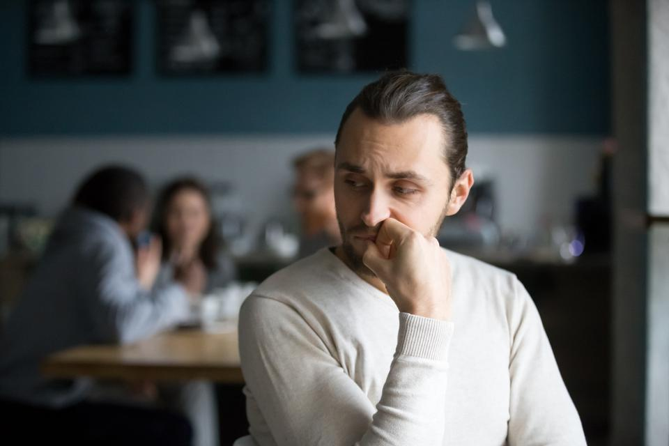 Upset male outcast feel lonely sitting alone in cafe