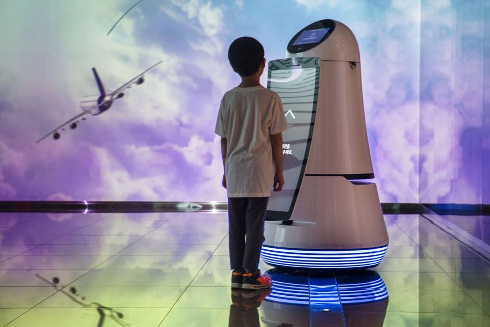 A young boy communicating with a robot that is on display at...