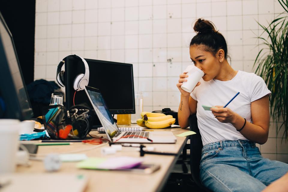 Mlada podjetnica pije kavo, ko sedi za mizo v majhni kreativni pisarni