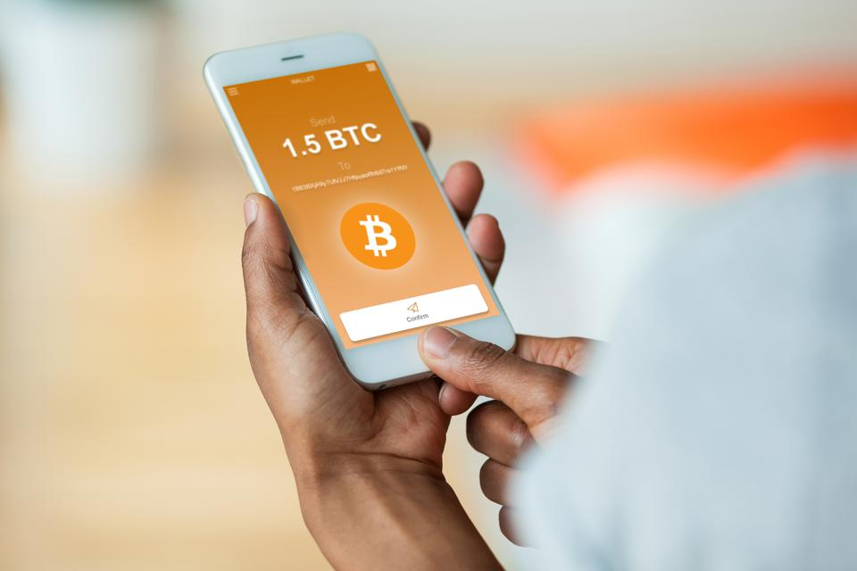 person sending a bitcoin btc crypto transaction using mobile phone wallet