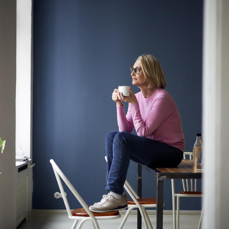 Mature woman at home with cup of coffee wondering if she can retire
