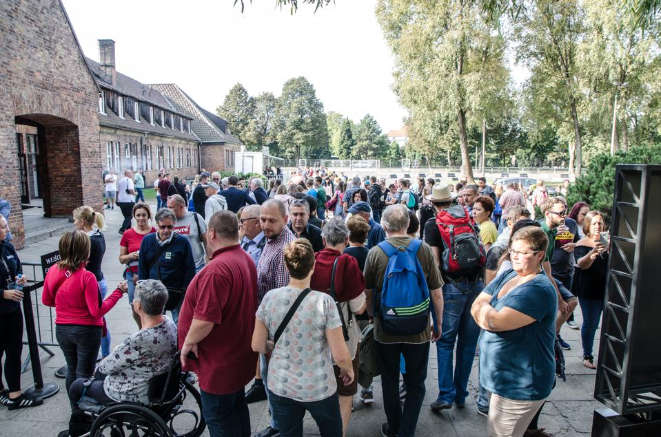 People waiting at the entrance of the Auschwitz concentration camp in Poland during summer day