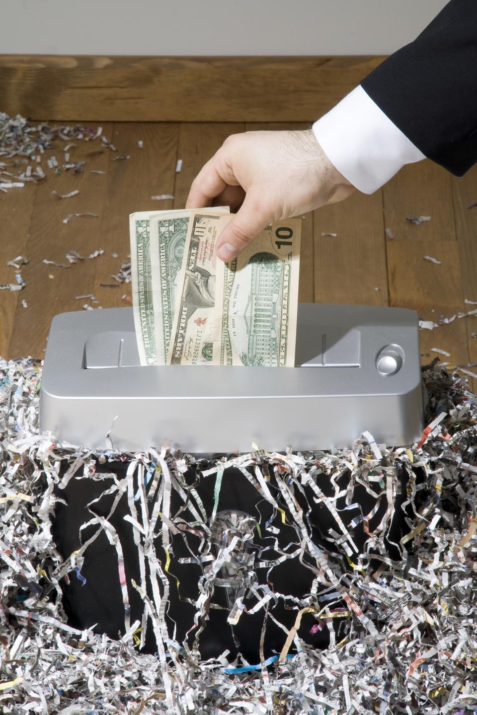 Man shredding one hundred dollar banknote