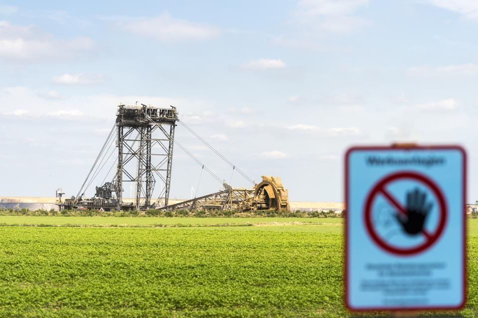 Germany, Garzweiler surface mine, warning sign and giant bucket-wheel excavator