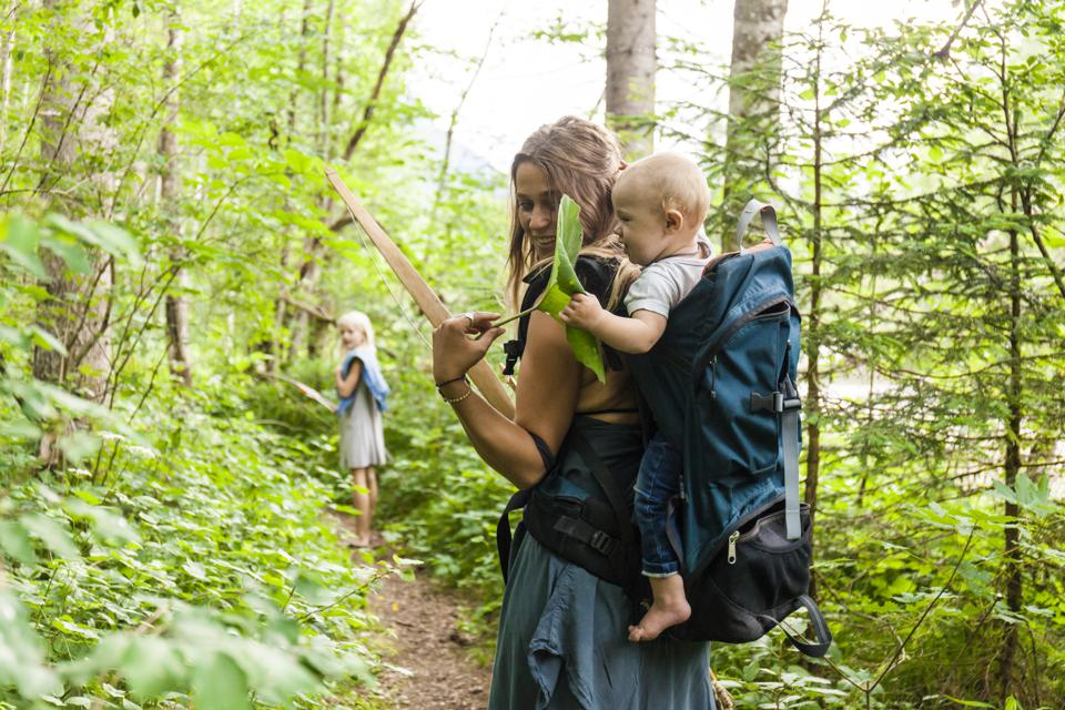 Woman hiking in the woods showing large leaf to baby boy in backpack