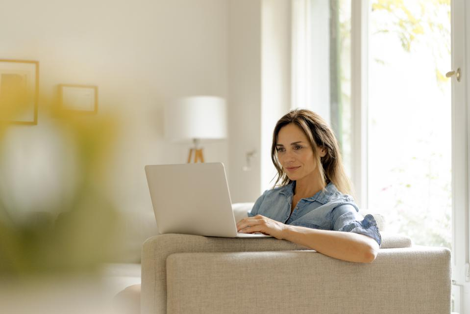 Mature woman sitting on couch at home using laptop