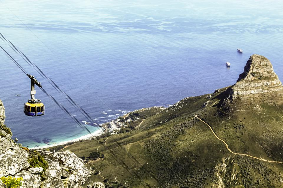 Top down view from Table Mountain of a cable car and the Lion's Head on the right and Atlantic Ocean in the background. It's one of the best places to visit.