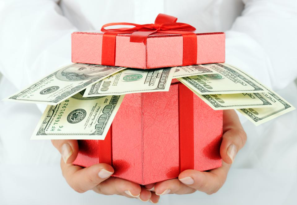 A red gift box with hundred dollar bills