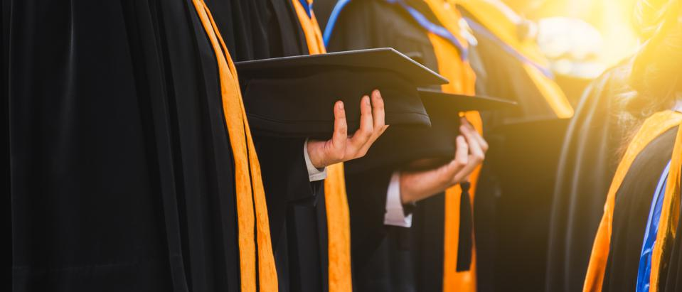 Close up of Graduate holding a hat.