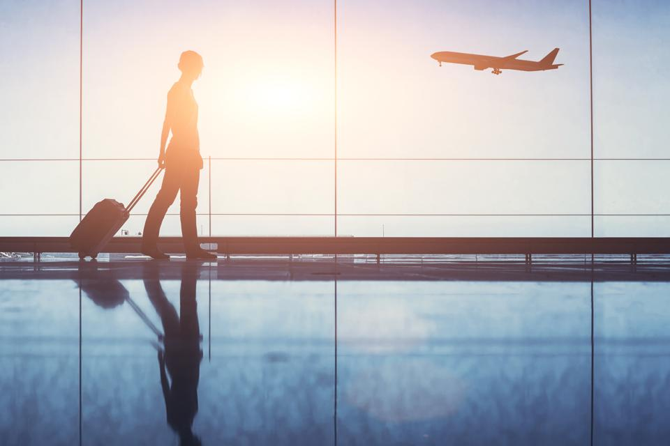 Travel. Silhouette of woman passenger with baggage in airport.