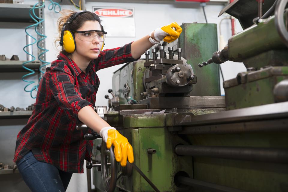 woman works at a milling machine in a Metal manufacturing company