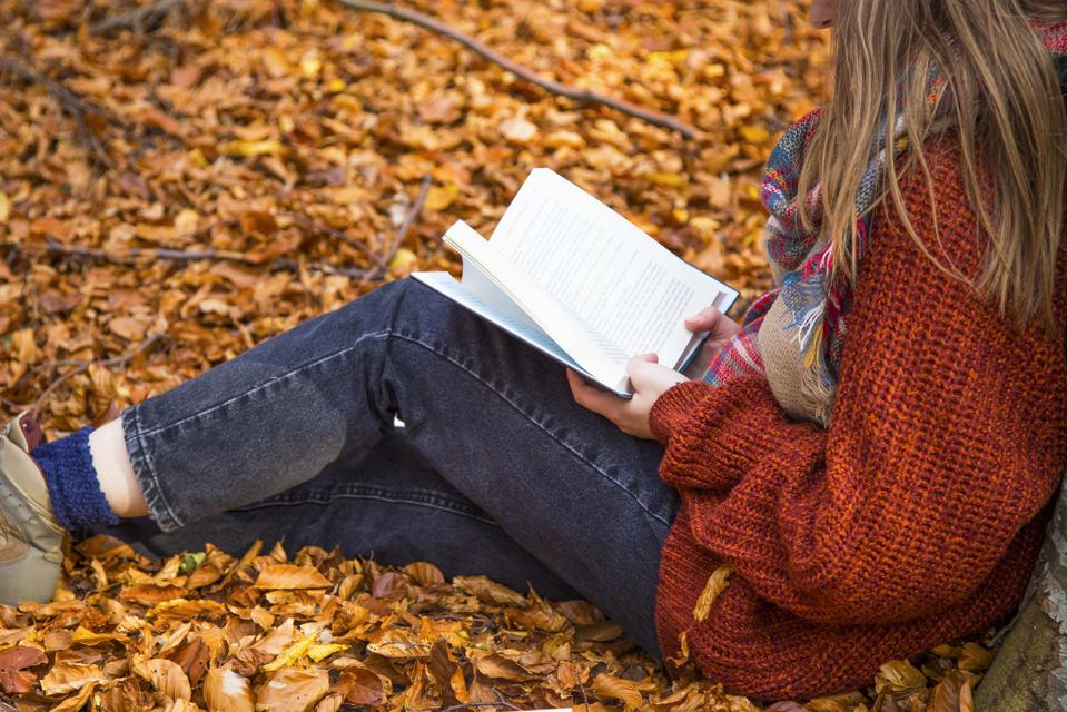 Girl reading in the autumn forest, fall concept outdoor reading