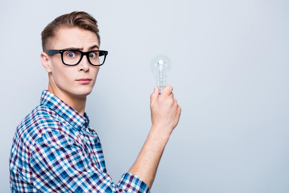 Profile side view photo of good-looking high school guy in checkered shirt and white t-shirt look at camera, hold lamp in hands isolated on light gray background with copy space for text