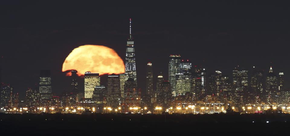 One day after the full Hunter's Moon, the moon rises behind lower Manhattan and One World Trade Center in New York City on October 25, 2018, as seen from Green Brook Township, New Jersey. (Photo by Gary Hershorn/Getty Images)
