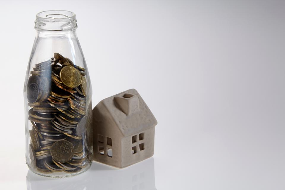 Close-Up Of Model Home And Coins Jar Over White Background