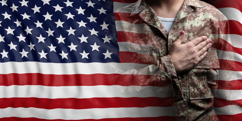 United States of America flag and soldier with hand on his heart.