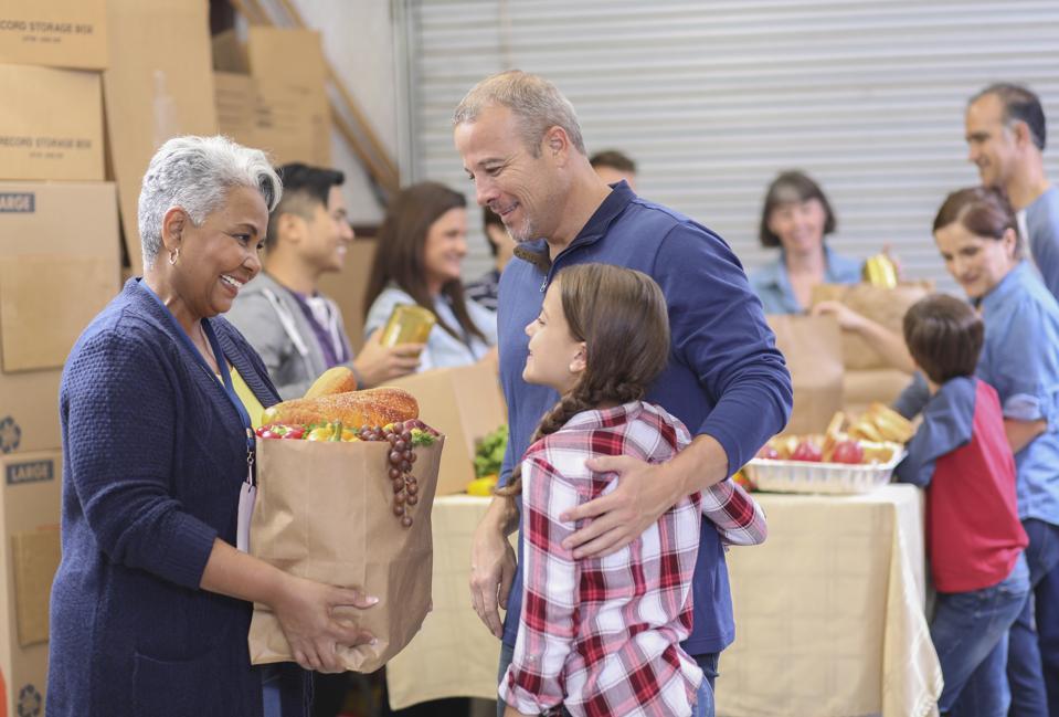 Multi-ethnic group of volunteers work at food bank.