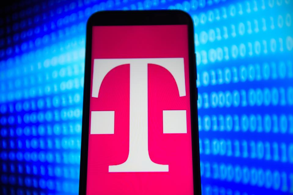T-Mobile logo is seen on an android mobile phone with binary code in the background