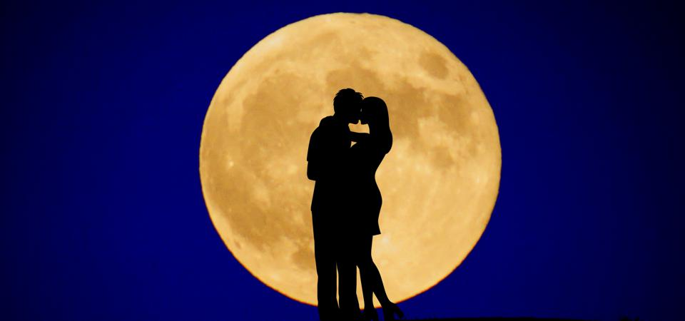 Two people kiss in front of a full moon.