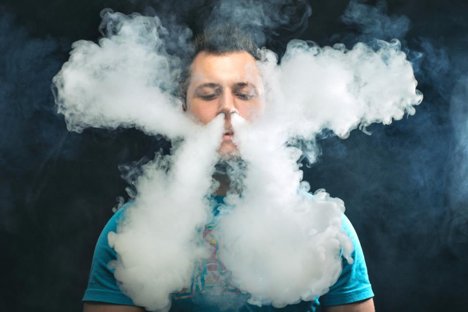 Vaping man and a cloud of vapor