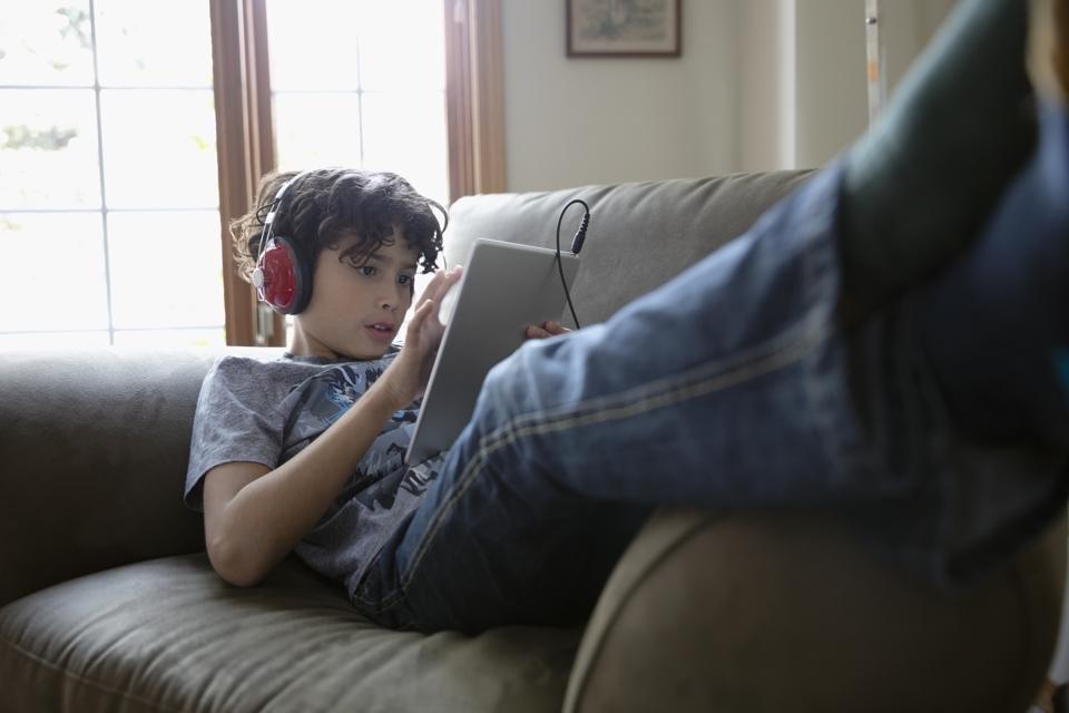 Latinx boy with headphones using digital tablet on sofa