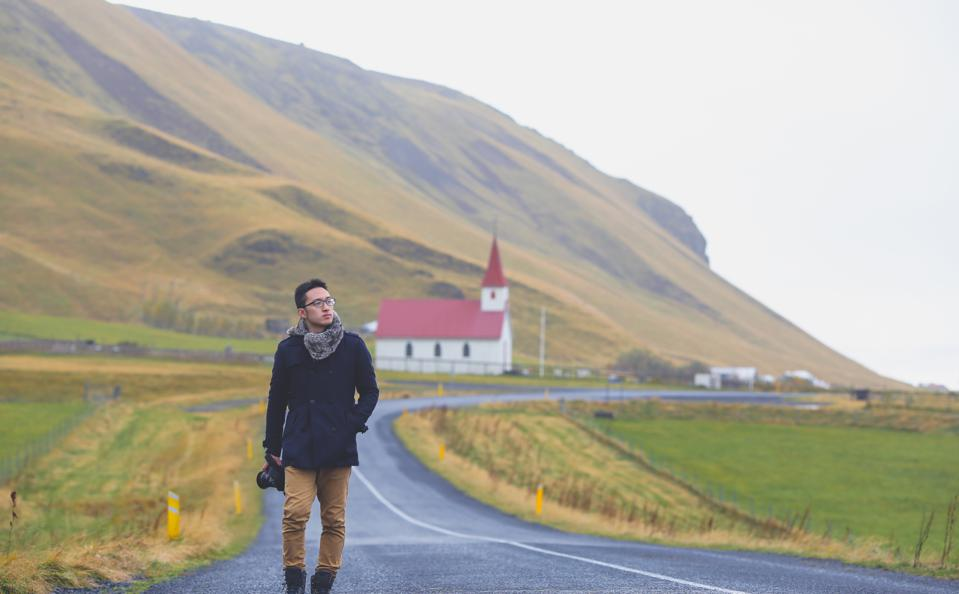 Photographer walking along a curved road in autumn, Vik, Southern Iceland