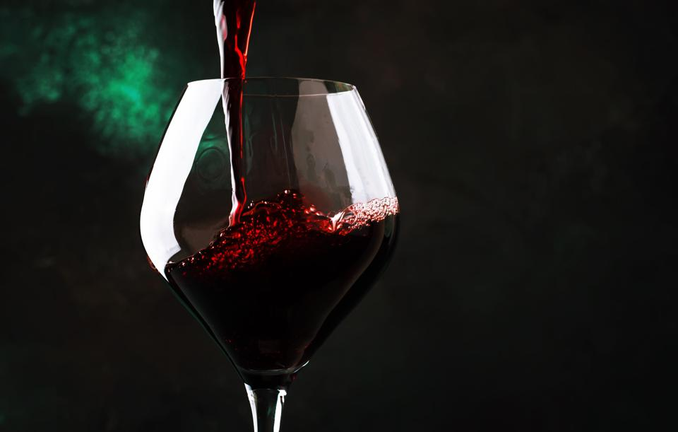 Red wine from grapes of pinot noir varieties poured into large wine glass