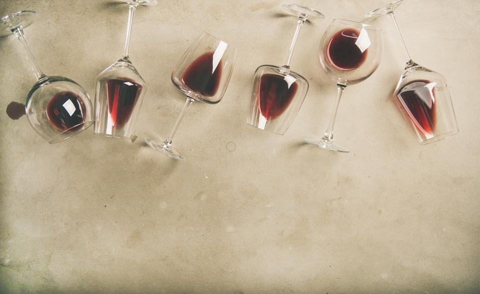 Red wine in glasses over grey concrete background, copy space