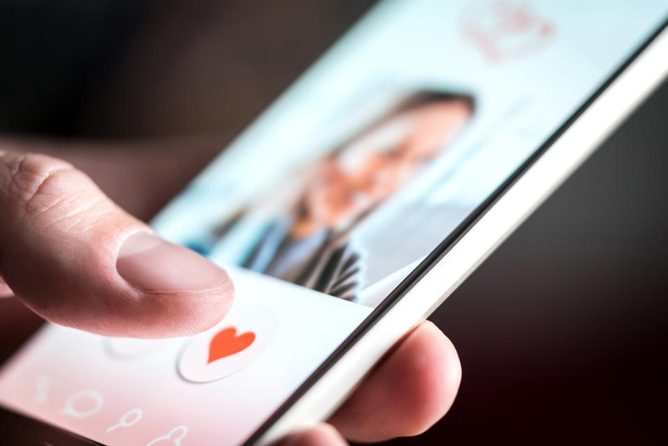 Dating app or site in mobile phone screen. Man swiping and liking profiles on relationship site or application. Single guy using smartphone to find love, partner and girlfriend.