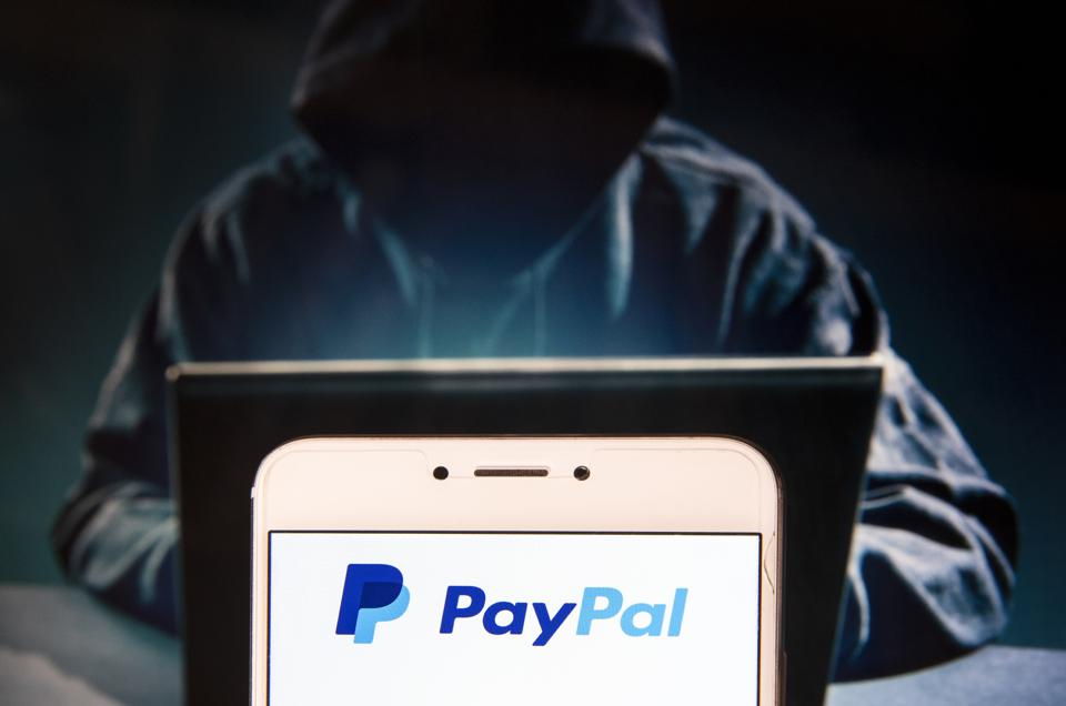 PayPal logo on a laptop with a sinister hooded hacker figure at the keyboard