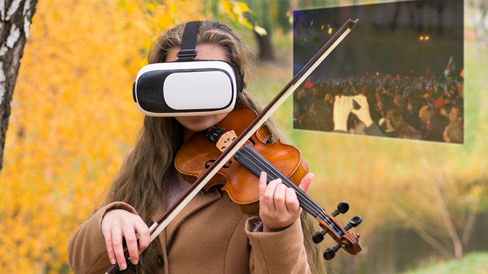 Girl playing the violin in virtual reality glasses in the autumn park at a lake background.