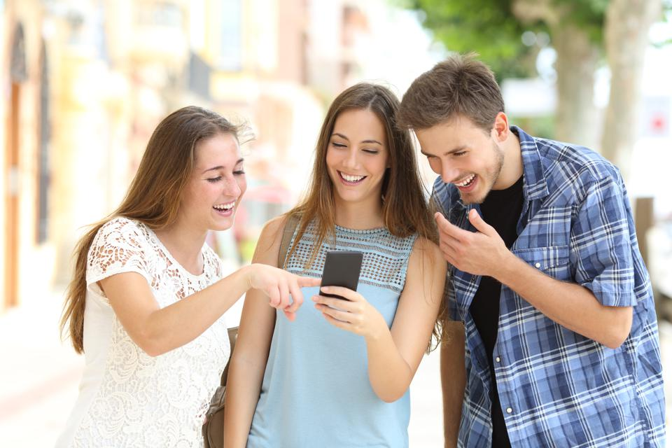 Friends watching smartphone content in the street