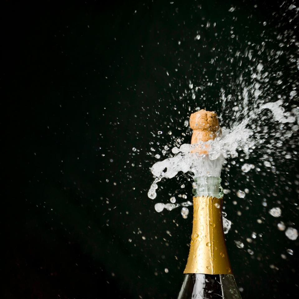 Champagne Exploding From Bottle Against Black Background