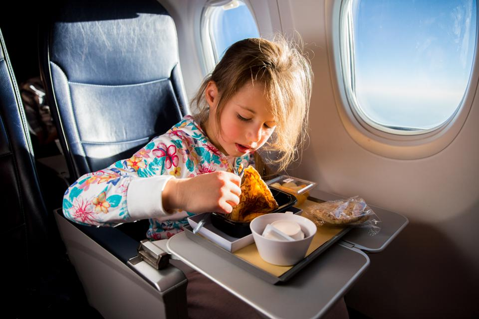 Child eating pancakes in airplane.