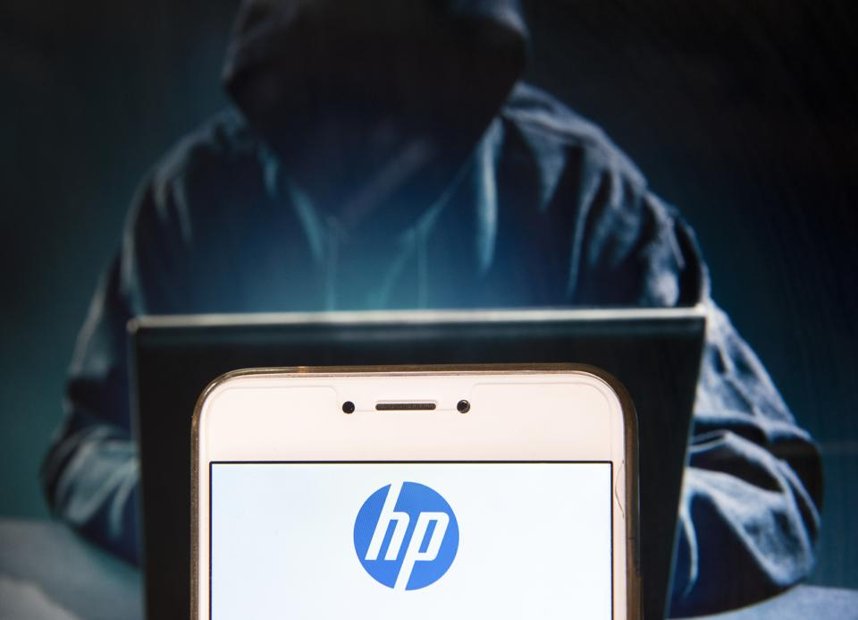 A hooded 'hacker' figure sits at a laptop with the HP logo displayed