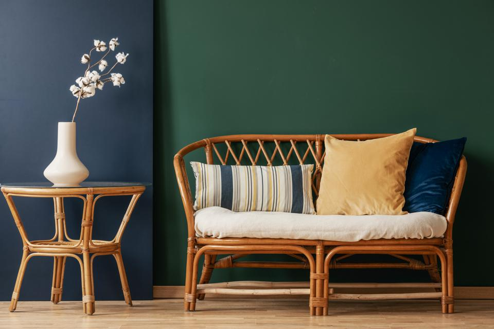 Flowers on natural table next to sofa with cushions in green and blue living room interior. Real photo