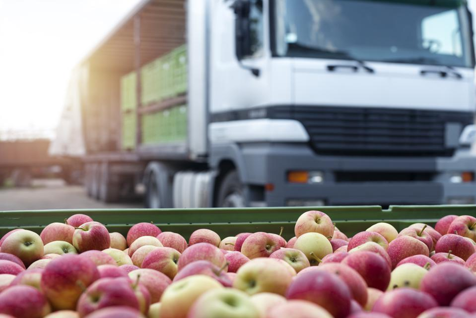 Apples and truck at food distribution center conceptualize supply and demand challenges.