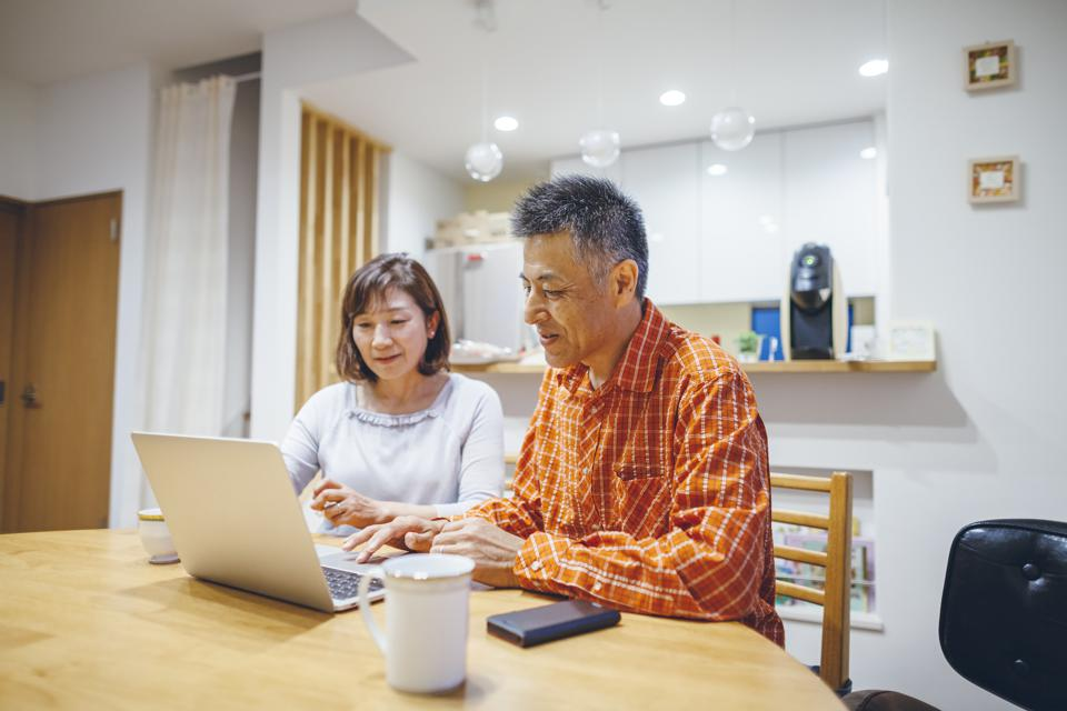 Married senior couple using laptop at home