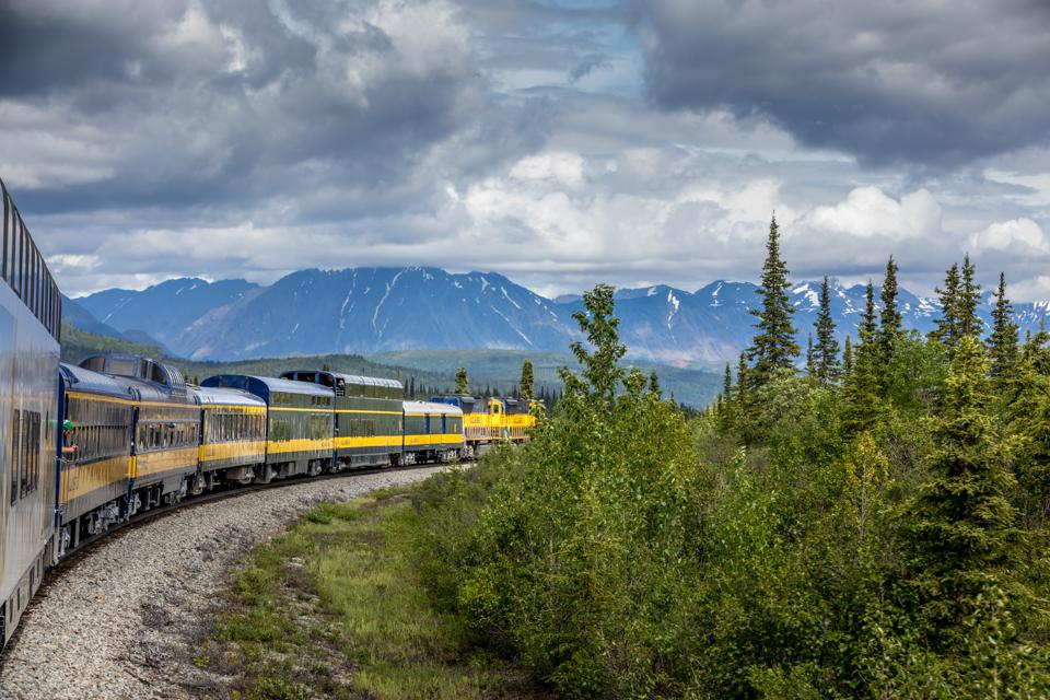 Train Passing By Mountains Against Cloudy Sky